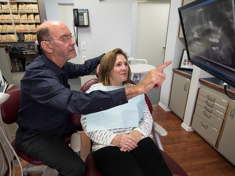 Dr. Alex Marrero reviewing an x-ray of a patient's teeth with her at Summercrest Dental, in Beaverton, OR
