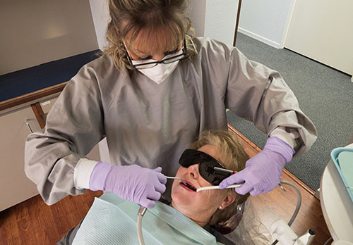 A dental hygenist at Summercrest Dental cleaning a patient's teeth while she relaxes in a dental chair